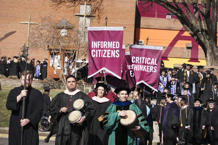 The traditional Augsburg University commencement procession begins from the quad to Si Melby.