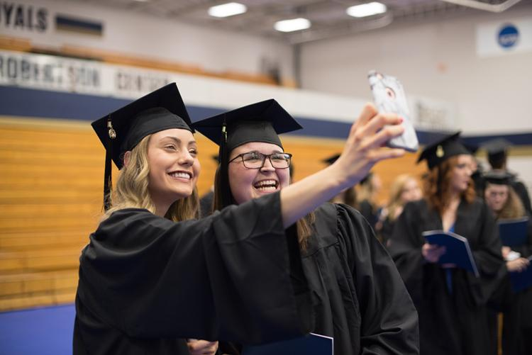Two graduating students from Bethel University take a selfie as they line up for commencement.