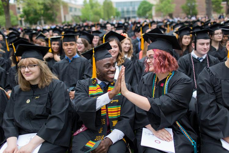 Hamline University grad given each other a high five.